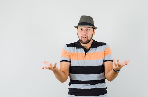 Jeune homme montrant un geste impuissant en t-shirt, chapeau et à la confusion.