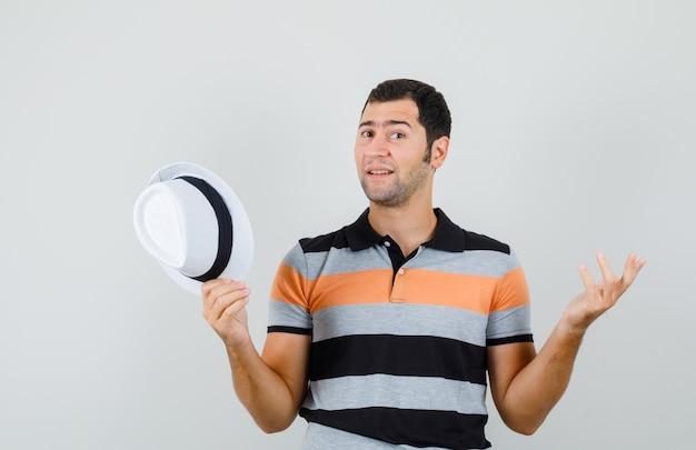 Jeune homme montrant un geste impuissant tout en tenant un chapeau en t-shirt, chapeau et à la perplexité. vue de face.