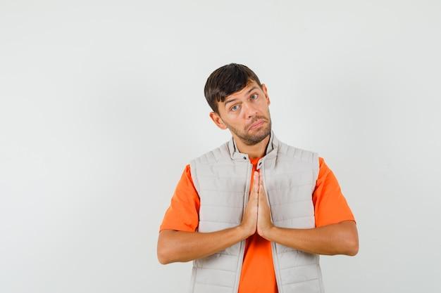 Jeune homme montrant le geste de namaste en t-shirt, veste et à l'humble.