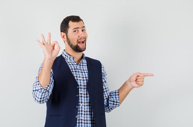 Jeune homme montrant le geste ok, pointant vers le côté en chemise, gilet et à la joyeuse