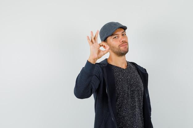Jeune homme montrant le geste ok en t-shirt, veste, casquette et à la vue de face, confiant.
