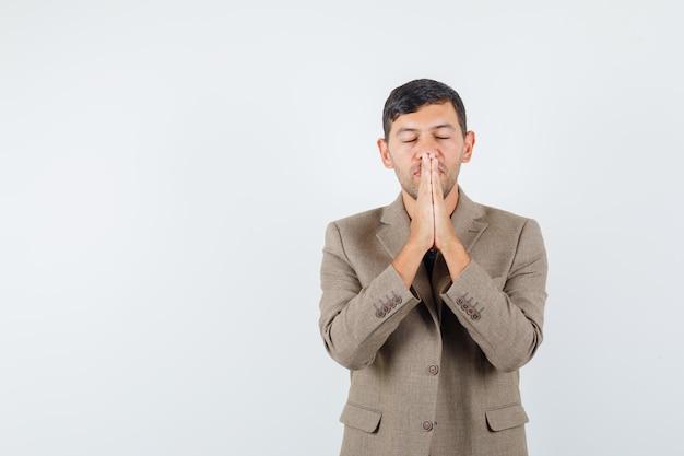 Jeune homme montrant un geste de prière en veste marron grisâtre et à la recherche de vœux pieux. vue de face. espace libre pour votre texte