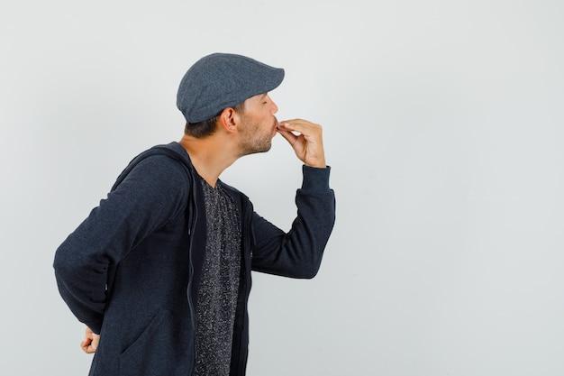 Jeune homme montrant un geste savoureux en t-shirt, veste, casquette et à ravi, vue de face.