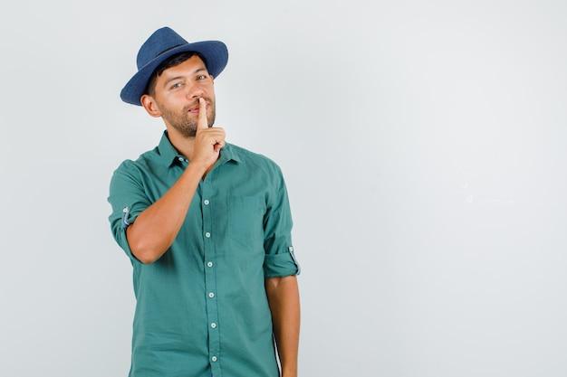 Jeune homme montrant le geste de silence et souriant en chemise