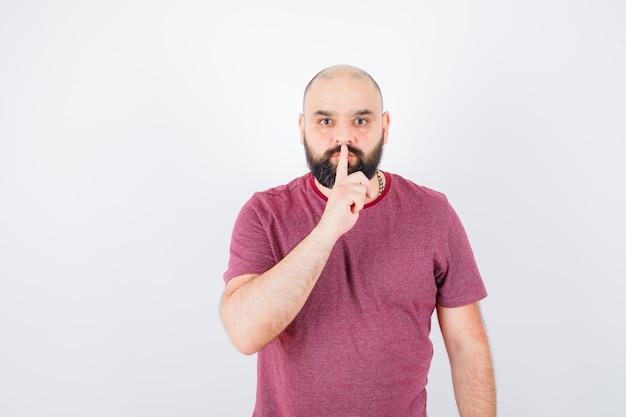 Jeune homme montrant un geste de silence en t-shirt rose et l'air sérieux, vue de face.
