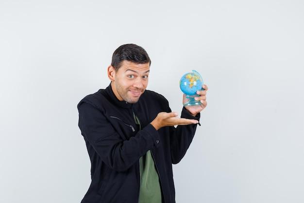 Jeune homme montrant le globe terrestre en t-shirt, veste et semblant joyeux, vue de face.
