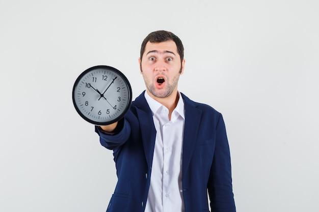 Jeune homme montrant une horloge murale en chemise et veste et à la surprise