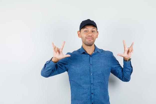 Jeune homme montrant je t'aime geste en chemise bleue, casquette et l'air joyeux, vue de face.