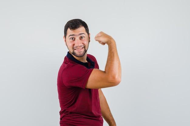 Jeune homme montrant le muscle du bras en t-shirt rouge et à la vue de face flexible.