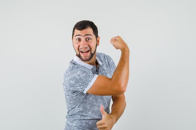 Jeune homme montrant les muscles des bras avec le pouce vers le haut en t-shirt et l'air heureux. vue de face.