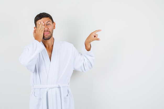 Jeune homme montrant de petite taille avec la main sur les yeux en vue de face de peignoir blanc.