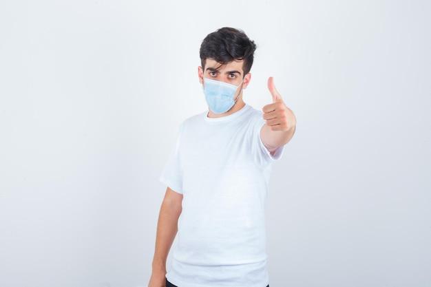 Jeune homme montrant le pouce en t-shirt blanc, masque et à l'air confiant