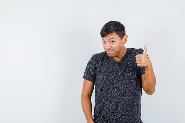 Jeune homme montrant le pouce en t-shirt noir et ayant l'air satisfait, vue de face. espace pour le texte