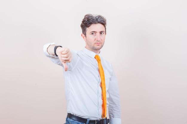 Jeune homme montrant le pouce vers le bas en chemise blanche, cravate, jeans