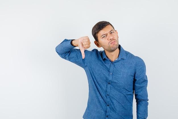 Jeune homme montrant le pouce vers le bas en chemise bleue et l'air insatisfait. vue de face.