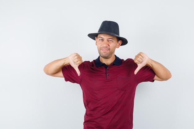 Jeune homme montrant le pouce vers le bas en chemise rouge, chapeau noir et l'air mécontent, vue de face.