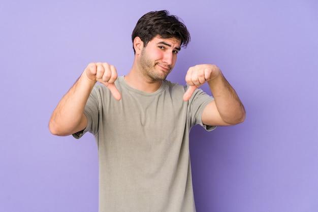 Jeune homme montrant le pouce vers le bas, concept de déception.
