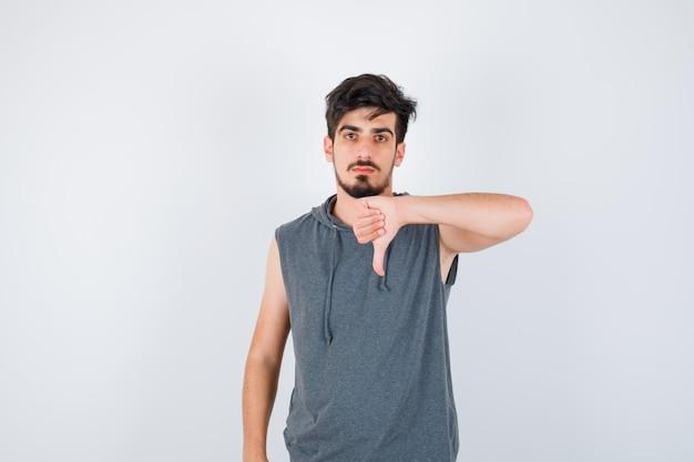 Jeune homme montrant le pouce vers le bas en t-shirt gris et à la grave