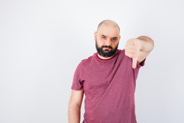 Jeune homme montrant le pouce vers le bas en t-shirt rose et l'air mécontent. vue de face.