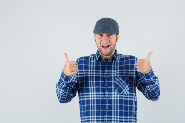 Jeune homme montrant le pouce vers le haut en chemise bleue, casquette et à la recherche de plaisir.