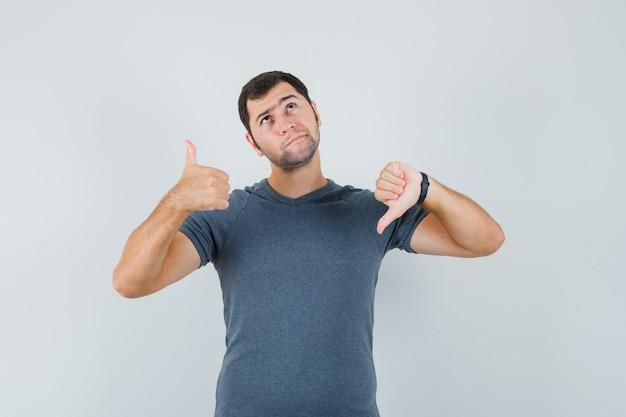 Jeune homme montrant les pouces de haut en bas en t-shirt gris et à la vue de face, hésitant.