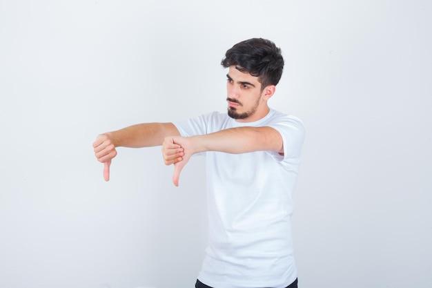 Jeune homme montrant les pouces vers le bas en t-shirt blanc et à l'air confiant