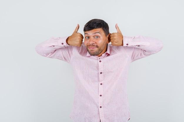 Jeune homme montrant les pouces vers le haut en chemise rose et regardant heureux, vue de face.