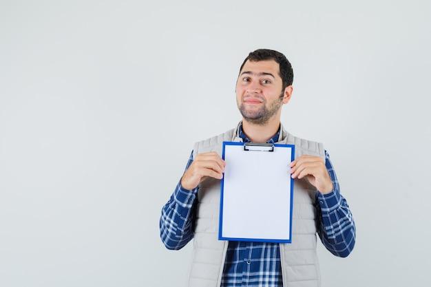 Jeune homme montrant le presse-papiers vierge en chemise, veste et à la recherche de calme. vue de face.