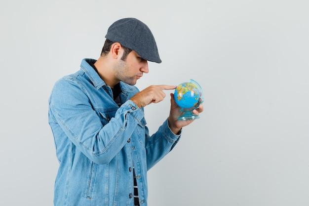 Jeune homme montrant quelque part sur mini globe en veste, casquette et à la recherche concentrée. vue de face.