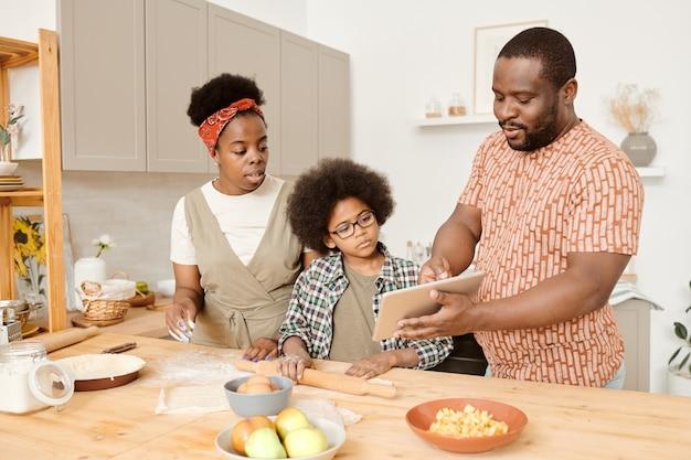 Jeune homme montrant une recette vidéo en ligne à sa femme et son fils