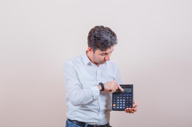 Jeune homme montrant les résultats sur la calculatrice en chemise blanche, vue de face de jeans.
