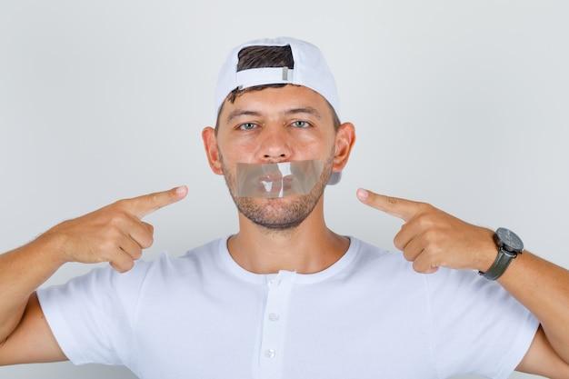 Jeune homme montrant sa bouche enregistrée en t-shirt blanc, casquette et à la vue calme, de face.
