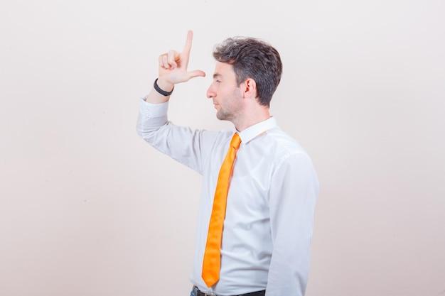 Jeune homme montrant le signe du perdant en chemise, jeans et à la colère