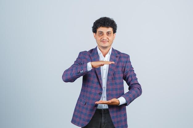 Jeune homme montrant un signe de grande taille dans une chemise, une veste et l'air confiant, vue de face.