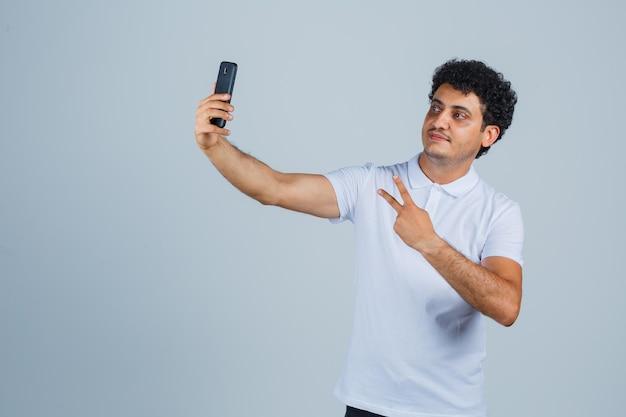 Jeune homme montrant le signe v tout en prenant un selfie en t-shirt blanc et l'air fier, vue de face.