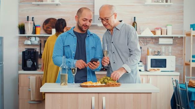 Jeune homme montrant à son père comment utiliser un smartphone moderne assis dans la cuisine et buvant un verre de vin blanc avant le dîner en famille. nouveau style de vie, utilisant la technologie pendant que les femmes préparent la guérison