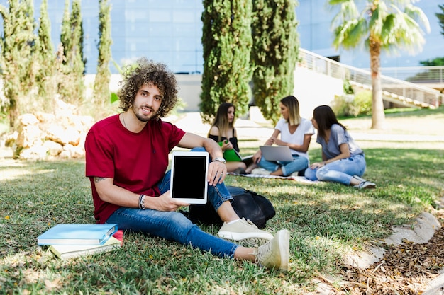 Jeune homme montrant la tablette à la caméra