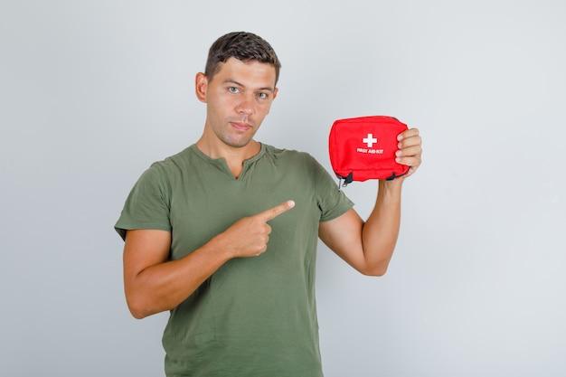 Jeune homme montrant une trousse de premiers soins en t-shirt vert armée et regardant prudemment, vue de face.