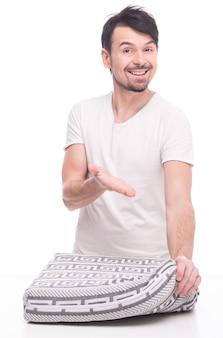 Jeune homme montre beau matelas sur blanc.