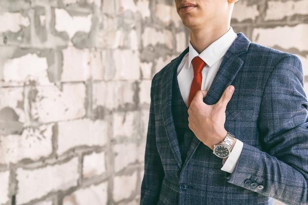 Jeune homme avec une montre-bracelet chère en costume à la mode sur fond de mur de béton, tonique
