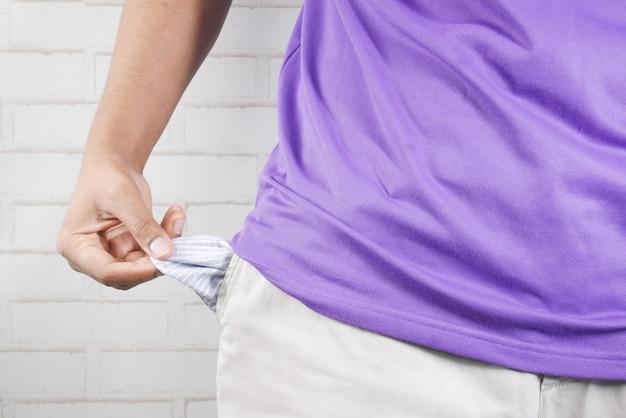 Le jeune homme montre la poche de pantalon vide avec l'espace de copie
