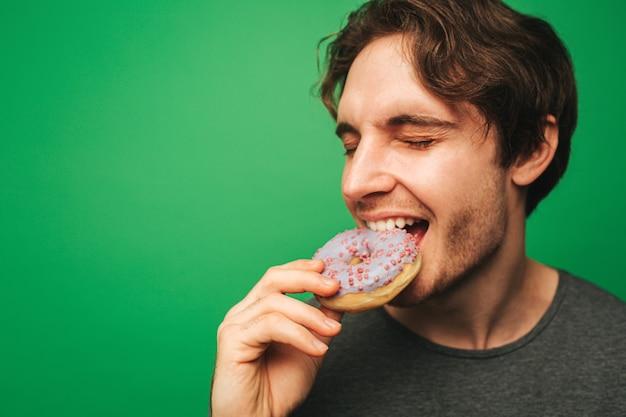 Jeune homme mord le beignet avec plaisir