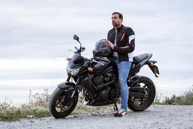 Jeune homme motard avec sa moto noire prête à conduire, en face de la mer