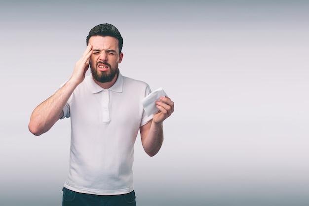 Jeune homme avec un mouchoir. un malade isolé a le nez qui coule. l'homme fait un remède contre le rhume.nerd porte des lunettes.