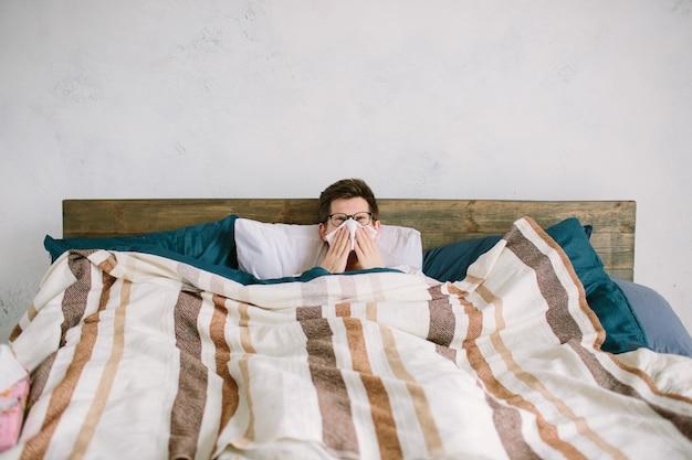 Jeune homme avec un mouchoir. un malade sur le lit a le nez qui coule. l'homme fait un remède contre le rhume