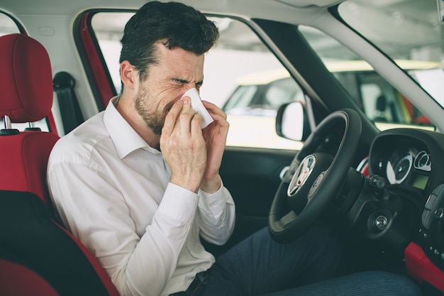 D'un jeune homme avec un mouchoir. le malade a le nez qui coule. l'homme fait un remède contre le rhume dans la voiture
