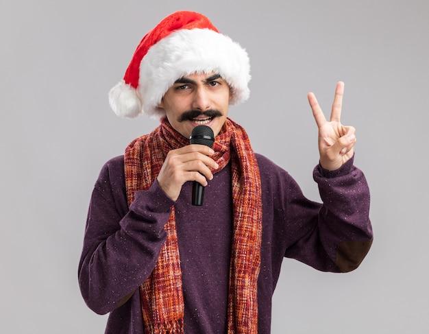 Jeune homme moustachu portant bonnet de noel de noël avec écharpe chaude autour de son cou parlant au microphone montrant v-sign