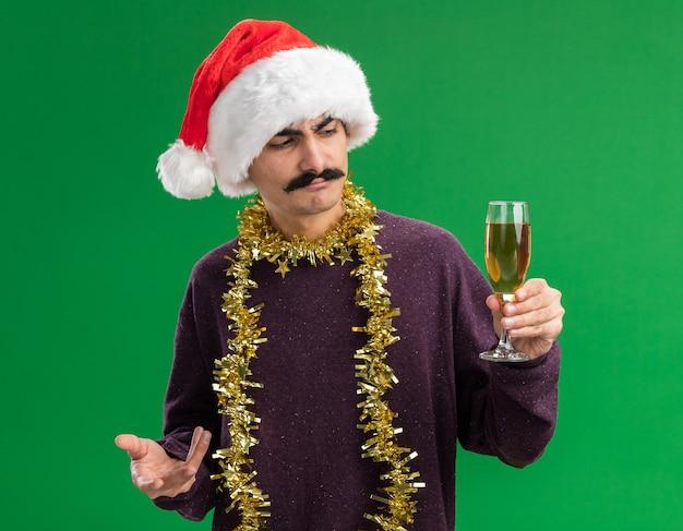 Jeune homme moustachu portant chapeau de père noël avec des guirlandes autour du cou tenant un verre de champagne en le regardant avec une expression confuse debout sur fond vert