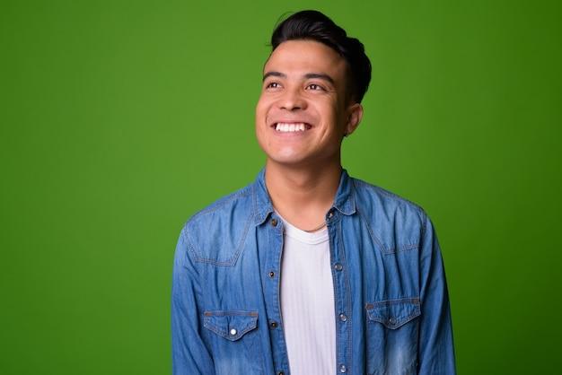Jeune homme multiethnique portant des vêtements intelligents sur fond vert