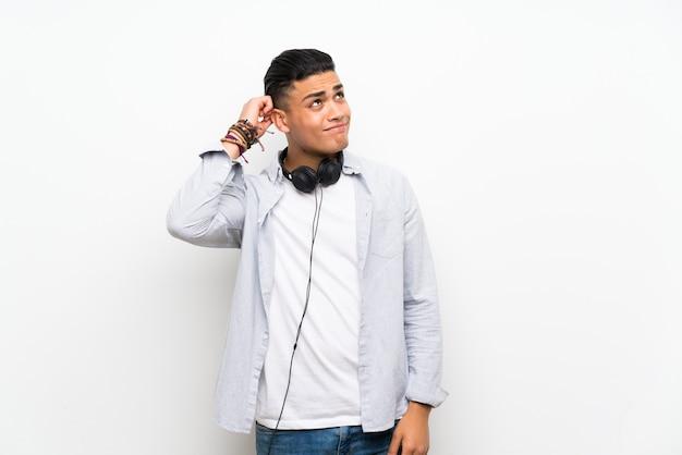 Jeune homme sur un mur blanc isolé avec des écouteurs ayant des doutes et avec une expression du visage confuse
